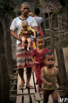 Refugees cross a wooden bridge at the Mae La refugee camp located near the Thai-Myanmar border some 550 kms northwest of Bangkok, in this file photo. Photo: AFP