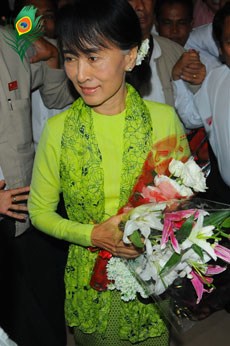 urma democracy leader Aung San Suu Kyi holds a bouquet of flowers as she walks through the international airport in Rangoon on Sunday, Sept. 16, 2012. She is expected to arrive in Washington on Monday, where she will receive the US Congressional Gold Medal and speak to various groups, followed by events in  New York City, Fort Wayne, the San Francisco Bay area, Los Angeles and other locations. Photo: Hein Htet / Mizzima